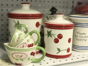 A set of jars and cups with a cherry design for sale at Sauk Centre STEP