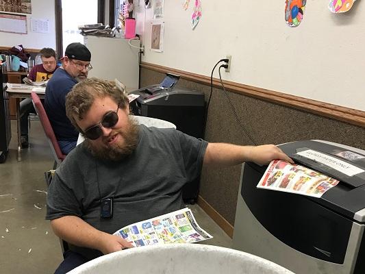 A worker shreds prepared newspaper for STEP Firestarters