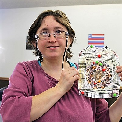 A STEP client proudly displays her finished art project.