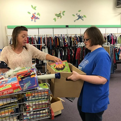 Baby Steps manager Sherry helps worker Amy sort books.