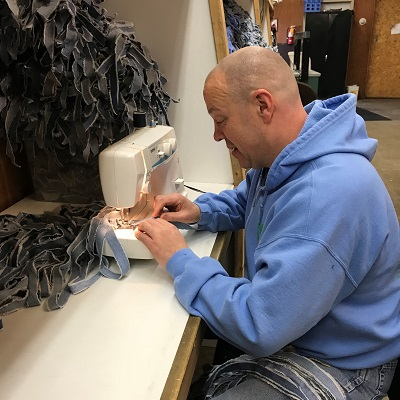 An employee concentrates on sewing fabric strips together to make STEP rugs.