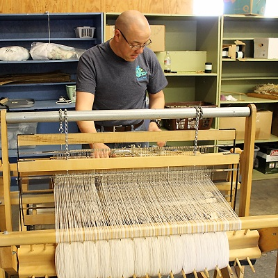 An employee working the loom at STEP Browerville